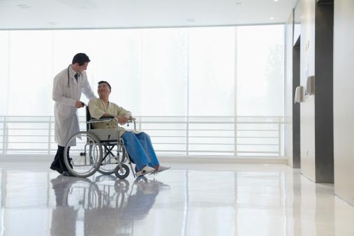 doctor wheeling man in wheelchair
