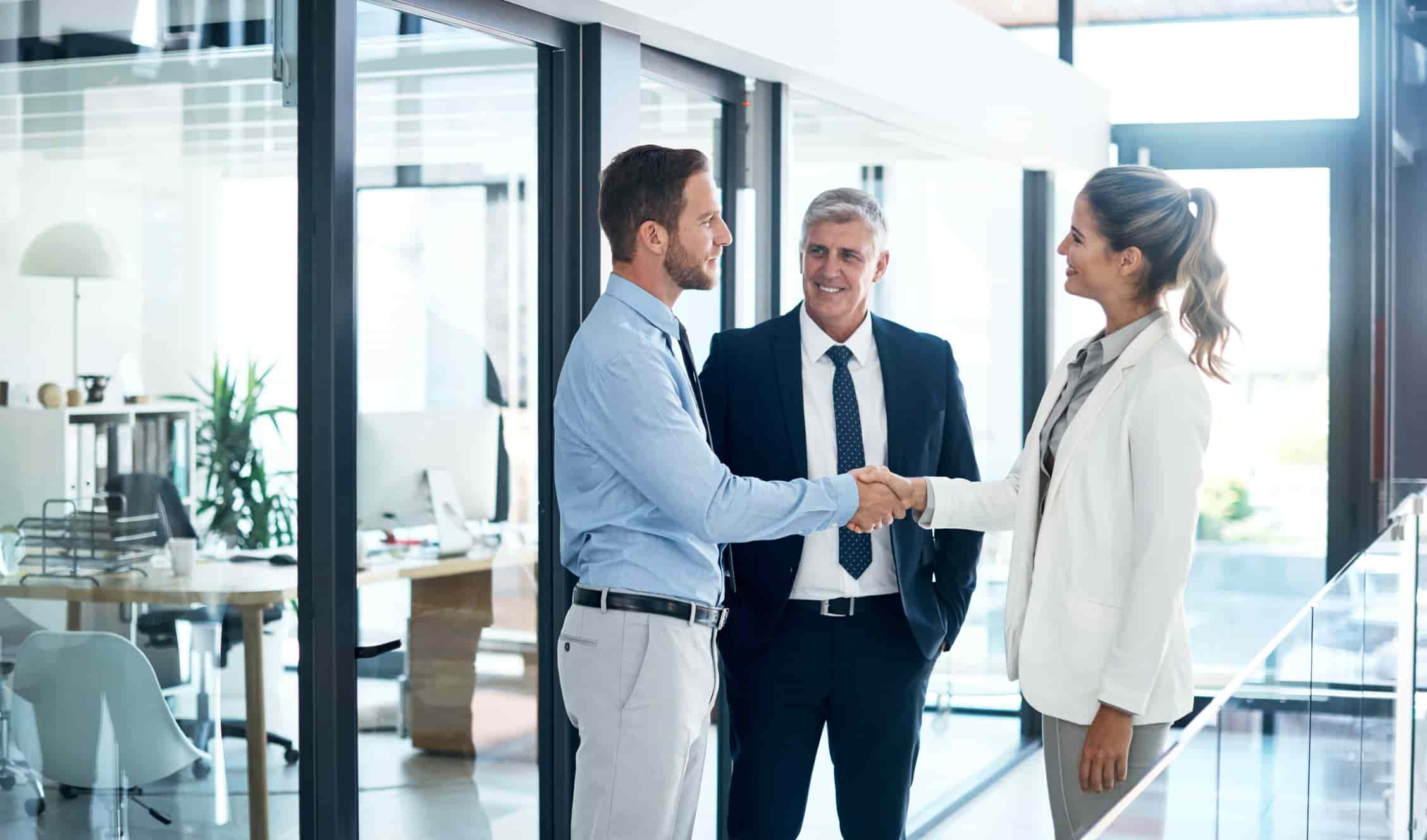 businessman and businesswoman shaking hands in a modern office